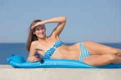 休息在海的蓝色比基尼泳装的运动女孩 免版税库存图片