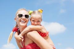 休息在海滩的愉快的家庭在夏天 图库摄影