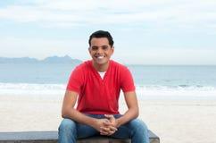休息在海滩的笑的拉丁人 免版税库存照片