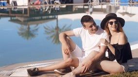 休息在游泳池附近的无忧无虑的恋人 太阳镜和帽子的女孩 夫妇在度假,晒日光浴,放松 Beackground棕榈 股票录像