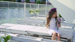 休息在湾口沙坝,嗅花的愉快的女孩和微笑 迟缓地 影视素材