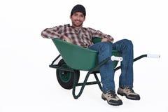 休息在独轮车的人。 库存照片