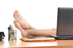 休息在的妇女与在办公室桌的脚一起使用 免版税库存图片
