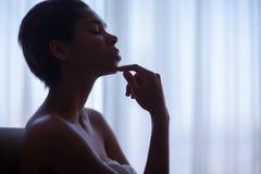 休息在窗口附近的美丽的妇女 免版税库存照片