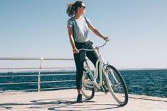 休息在自行车乘驾期间的亭亭玉立的时髦的年轻女人 免版税库存图片