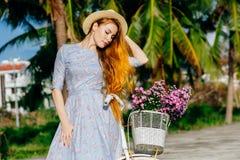 休息在自行车附近的礼服的美丽的红色头发妇女 库存照片