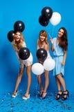 休息在蓝色背景的党的三个美丽的女孩 免版税库存照片