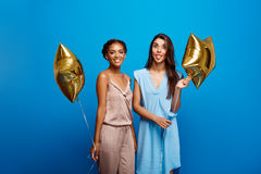 休息在蓝色背景的党的两个女孩画象  免版税库存图片