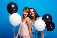休息在蓝色背景的党的两个女孩画象  库存照片