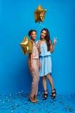 休息在蓝色背景的党的两个女孩画象  免版税图库摄影