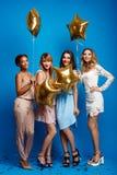 休息在蓝色背景的党的四个美丽的女孩 免版税库存照片
