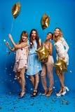 休息在蓝色背景的党的四个美丽的女孩 图库摄影