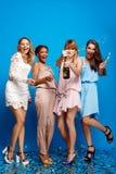 休息在蓝色背景的党的四个美丽的女孩 免版税库存图片