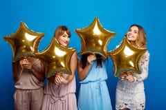 休息在蓝色背景的党的四个美丽的女孩 库存照片
