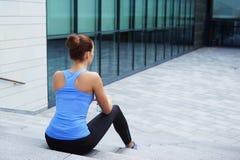 休息在训练以后的年轻人、适合和运动的妇女 健身,体育,都市跑步和健康生活方式概念 免版税库存照片
