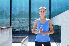 休息在训练以后的年轻人、适合和运动的妇女 健身,体育,都市跑步和健康生活方式概念 图库摄影