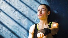 休息在训练以后的画象美丽的年轻拳击妇女在猛击在健身房以后 免版税库存图片