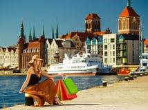 休息在购物的坐的时髦的女人与袋子以后 免版税库存图片
