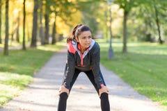 休息在跑步以后的微笑的妇女在公园 免版税图库摄影