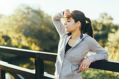 休息在跑步以后的美丽的妇女户外 免版税库存照片