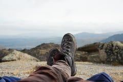 休息在跟踪反对山和谷背景的山的起动的一个人的腿与喧闹的云彩 库存图片