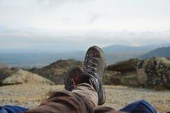休息在跟踪反对山和谷背景的山的起动的一个人的腿与喧闹的云彩 库存照片