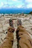 休息在跟踪反对山和谷背景的山的起动的一个人的腿与远足起动的喧闹的云彩 库存图片