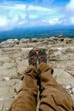 休息在跟踪反对山和谷背景的山的起动的一个人的腿与远足起动的喧闹的云彩 图库摄影