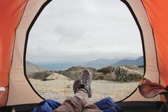 休息在跟踪在旅行帐篷的山的起动的一个人的腿反对山和谷背景与 图库摄影