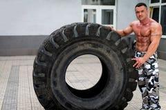 休息在轮胎轻碰以后的肌肉人 免版税库存照片