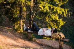 休息在远足的人说谎在一个长木凳的旅行期间在远足本质上的森林里 库存图片