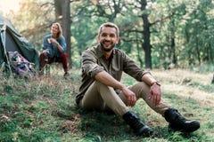 休息在野营的愉快的年轻家庭 免版税图库摄影