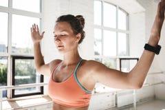 休息在锻炼之间的Taned适合的女孩接近室内晴朗的健身房 库存图片