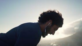 休息在锻炼以后的一个微笑的男性赛跑者在户外 免版税图库摄影