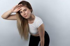 休息在锻炼或奔跑以后的年轻运动女学生 厕所 库存照片