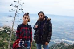 休息在长的路以后的年轻远足者站立在山 图库摄影