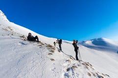 休息在长途以后的一个小组登山人远足和享受激动人心的景色 库存图片