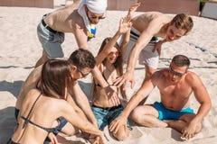 休息在集合之间的间隔时间的小组白种人朋友在海滩法院 库存照片