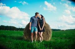 休息在领域的恋人在干草堆附近 库存图片