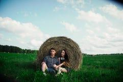休息在领域的恋人在干草堆附近 图库摄影