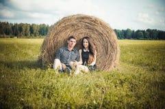 休息在领域的恋人在干草堆附近 免版税图库摄影