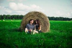 休息在领域的恋人在干草堆附近 免版税库存照片