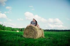 休息在领域的恋人在干草堆附近 免版税库存图片