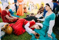 休息在阴影t的中世纪文化节日的参加者 免版税库存照片