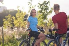 休息在晴朗的自然的森林周围的白种人骑自行车的人 免版税库存图片