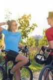 休息在晴朗的自然的森林周围的白种人骑自行车的人 免版税库存照片