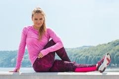 休息在锻炼由海,健康活跃生活方式以后的运动的衣裳的亭亭玉立的女孩 免版税库存照片