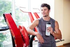 休息在锻炼以后的一个微笑的爱好健美者的画象在健身房 免版税库存照片
