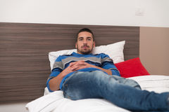 休息在他的卧室的可爱的人 库存图片