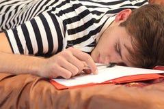 休息在他的卧室的疲乏的学生 图库摄影